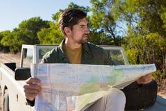 拿着在公路车辆的人地图 免版税库存图片