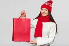 拿着在兴奋的惊奇的愉快的妇女红色袋子,购物 冬天销售的圣诞节女孩与礼物,隔绝在灰色 免版税库存图片
