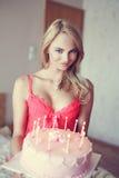 拿着在内衣的性感的白肤金发的妇女生日蛋糕 库存图片