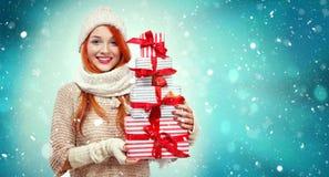 拿着在冬天背景的购物妇女礼物盒与雪在黑星期五,圣诞节和新年假日 销售额 免版税图库摄影