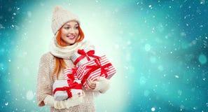 拿着在冬天背景的购物妇女礼物盒与雪在黑星期五,圣诞节和新年假日 销售额 免版税库存图片