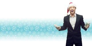 拿着在冬天backgr的圣诞老人帽子的年轻商人金钱 免版税库存图片