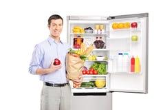 拿着在冰箱前面的微笑的人一个袋子 库存照片
