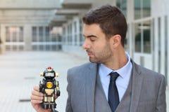 拿着在办公室空间的商人一个机器人 免版税库存照片