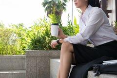 拿着在办公楼之外的女实业家咖啡 美丽 库存图片