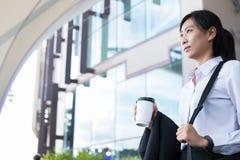 拿着在办公楼之外的女实业家咖啡 美丽 免版税库存照片