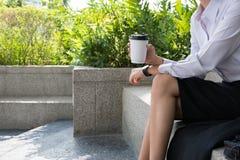 拿着在办公楼之外的女实业家咖啡 美丽 库存照片