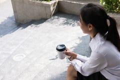 拿着在办公楼之外的女实业家咖啡 美丽 图库摄影