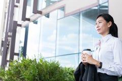 拿着在办公楼之外的女实业家咖啡 美丽 免版税库存图片