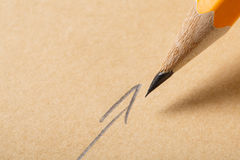 拿着在包装纸背景的一支铅笔,画与箭头的标志的铅笔 免版税库存照片