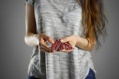拿着在包裹的女孩红色药片 特写镜头 在水泡的片剂 库存照片