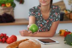拿着在厨房内部的女性手特写镜头绿色苹果 许多菜和其他膳食在玻璃桌上是 免版税库存照片