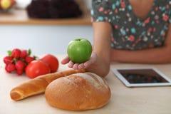 拿着在厨房内部的女性手特写镜头绿色苹果 许多菜和其他膳食在玻璃桌上是 免版税图库摄影