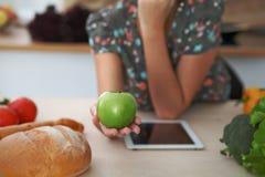 拿着在厨房内部的女性手特写镜头绿色苹果 许多菜和其他膳食在玻璃桌上是 库存照片