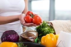 拿着在厨房worktop的一位白种人厨师的女性手红色蕃茄束用新鲜的杂货和黑麦面包对此 免版税库存图片