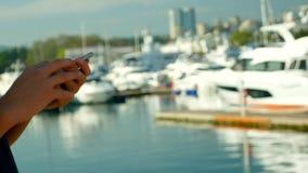 拿着在口岸被弄脏的背景的男性手智能手机与游艇的 免版税库存照片