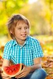 拿着在叶子的男孩画象西瓜 库存照片
