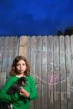 拿着在后院木头篱芭的儿童女孩小狗 免版税库存照片