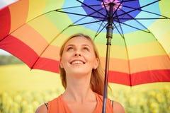 拿着在向日葵领域和蓝色云彩天空背景的快乐的美丽的女孩多彩多姿的伞 免版税图库摄影