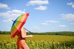 拿着在向日葵领域和蓝色云彩天空背景的快乐的美丽的女孩多彩多姿的伞 免版税库存照片