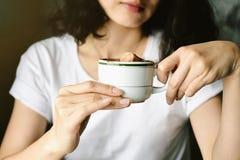 拿着在咖啡咖啡馆,妇女的行家时髦女孩一个咖啡杯给能量早晨开始的一个热的咖啡杯 免版税库存照片