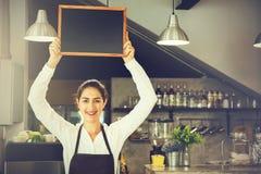 拿着在咖啡店里面的barista围裙的美丽的白种人妇女空的黑板标志 免版税图库摄影