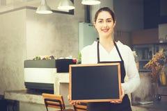 拿着在咖啡店里面的barista围裙的美丽的白种人妇女空的黑板标志 库存图片