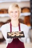 拿着在咖啡馆的女服务员面包盘子 免版税库存照片