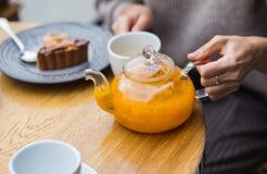 拿着在咖啡馆的妇女一个茶壶 免版税图库摄影