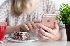 拿着在咖啡馆的妇女手中iPhone 6S罗斯金子 免版税库存照片