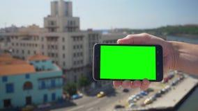 拿着在哈瓦那古巴上的绿色屏幕智能手机 影视素材