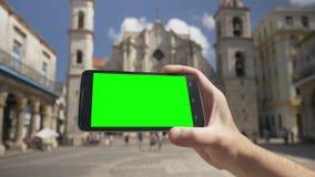 拿着在哈瓦那大教堂附近的绿色屏幕智能手机 股票视频