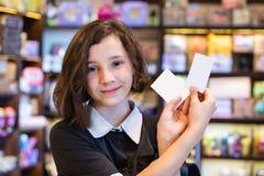 拿着在商店背景的逗人喜爱的青少年女孩白色卡片  免版税库存照片