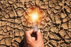 拿着在土壤的手电灯泡干旱 太阳概念的力量 库存图片