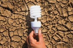 拿着在土壤的手电灯泡干旱 太阳概念的力量 免版税图库摄影