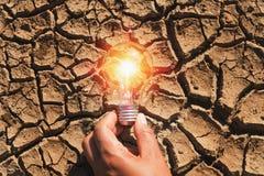 拿着在土壤的手电灯泡干旱 概念力量太阳能 免版税库存图片