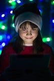 拿着在圣诞老人` s帽子的女孩片剂个人计算机 免版税库存图片