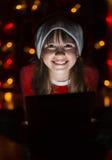 拿着在圣诞老人` s帽子的女孩片剂个人计算机 库存图片