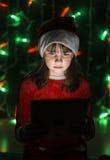 拿着在圣诞老人` s帽子的女孩片剂个人计算机 库存照片