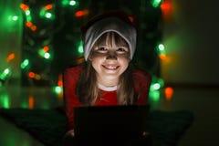 拿着在圣诞老人` s帽子的女孩片剂个人计算机 免版税图库摄影