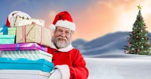 拿着在圣诞节冬天风景的圣诞老人礼物与圣诞树 免版税库存照片