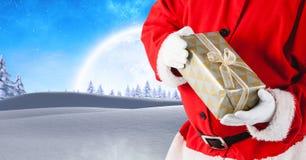 拿着在圣诞节冬天风景的圣诞老人礼物 免版税图库摄影