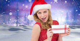 拿着在圣诞节冬天风景的女性圣诞老人礼物 库存图片