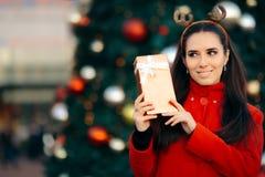 拿着在圣诞节前面的妇女礼物盒装饰了树 图库摄影