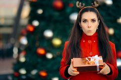 拿着在圣诞节前面的妇女礼物盒装饰了树 免版税库存图片