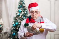拿着在圣诞节背景的老人金钱 库存图片