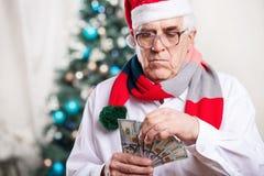 拿着在圣诞节背景的老人金钱 免版税库存照片