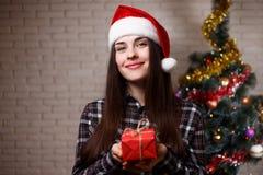 拿着在圣诞节tr的圣诞老人盖帽的年轻逗人喜爱的妇女一个礼物盒 免版税库存照片