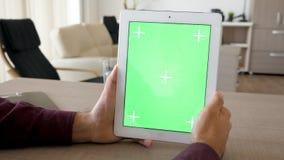 拿着在垂直位置的一台数字式片剂个人计算机与绿色屏幕色度嘲笑 股票视频