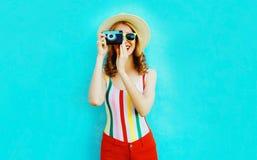 拿着在夏天草帽的五颜六色的愉快的微笑的年轻女人减速火箭的照相机获得在蓝色墙壁上的乐趣 免版税库存照片